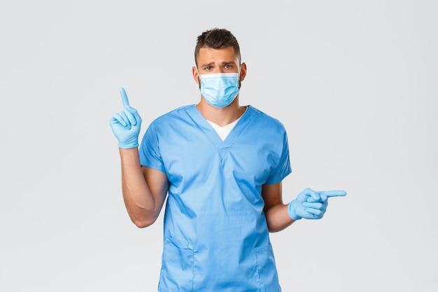 Gezondheidswerkers, covid-19, coronavirus en virusconcept. verdrietig en vermoeide dokter, spaanse verpleger in scrubs, medisch masker en handschoenen die zijwaarts wijzen, uitgeput voelen tijdens de nachtdienst