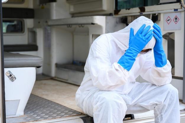 Gezondheidswerkers die werken aan ambulances die pbm-beschermende kleding dragen. dokterassistenten zitten verdrietig en moe op de ambulance.