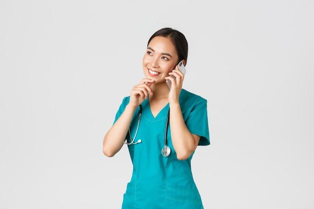 , gezondheidswerkers en het voorkomen van virusconcept. portret van lachende aziatische vrouwelijke arts, stagiair in scrubs praten aan de telefoon en op zoek attent, denken of een keuze maken.