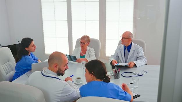 Gezondheidswerkers hebben een bijeenkomst in de vergaderruimte van het ziekenhuis over symptomen van patiënten die röntgenfoto's analyseren. kliniekdeskundige therapeut in gesprek met collega's over ziekte, medisch professional