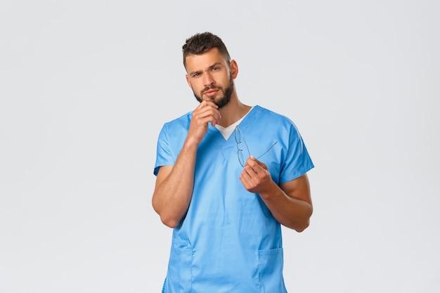Gezondheidswerkers, medicijnen, covid-19 en pandemisch zelfquarantaineconcept. ernstige en attente slimme verpleger, dokter in blauwe scrubs, wrijf baard en kijk geïnteresseerd, grijze achtergrond