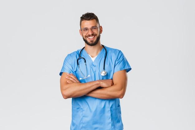 Gezondheidswerkers, medicijnen, covid-19 en pandemisch zelfquarantaineconcept. glimlachende aantrekkelijke arts in scrubs en bril, stethoscoop over nek, kruisarmen op de borst, klaar om patiënten te helpen