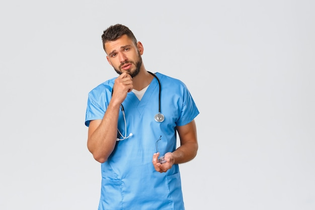 Gezondheidswerkers, medicijnen, covid-19 en pandemisch zelfquarantaineconcept. vermoeide jonge dokter in blauwe scrubs, verpleger luistert naar patiënt met bezorgd, gefocust gezicht met weinig vermoeidheid