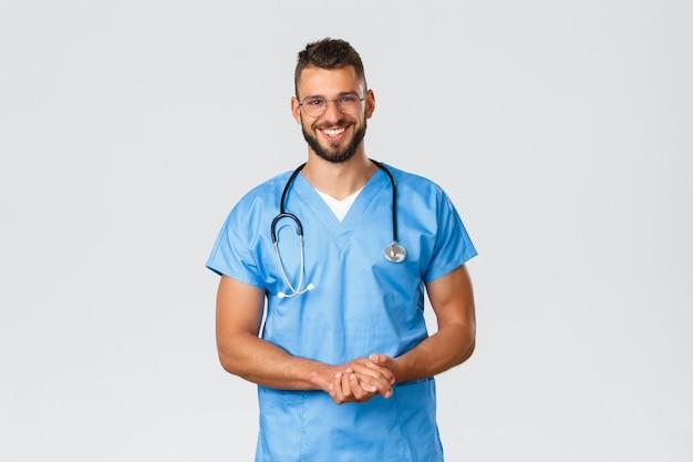 Gezondheidswerkers, medicijnen, covid-19 en pandemisch zelfquarantaineconcept. vrolijk lachende spaanse verpleger, arts in er met scrubs en bril, praten met de patiënt in de kliniek
