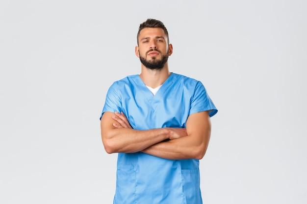 Gezondheidswerkers, medicijnen, covid-19, pandemisch zelfquarantaineconcept. zelfverzekerde sterke, serieus ogende spaanse arts, verpleger in blauwe kleding, zelfverzekerd op de borst gekruist, patiënten redden.