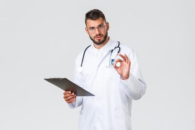Gezondheidswerkers, medische verzekering, klinieklab en covid-19-concept. knappe serieuze dokter in witte jas, bril en klembord, laat een goed teken zien, verzeker de tests in orde, de resultaten zijn goed.