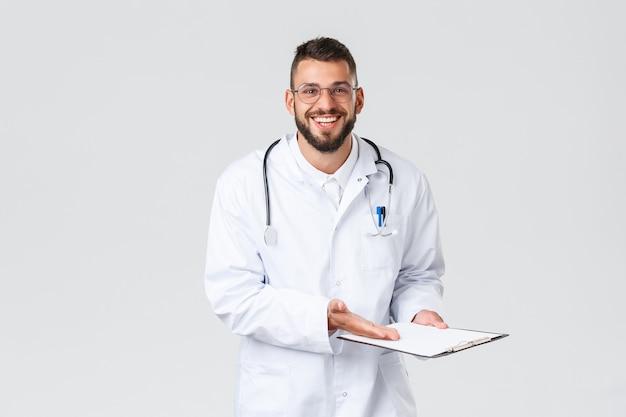 Gezondheidswerkers, medische verzekering, klinieklab en covid-19-concept. vrolijke en opgeluchte knappe dokter onthult goede resultaten van testscreening, glimlachende patiënt, wijs naar klembord