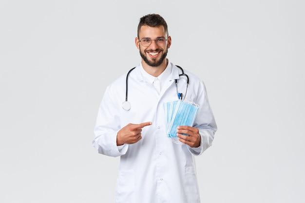 Gezondheidswerkers, medische verzekering, pandemie en covid-19 concept. vrolijke, glimlachende knappe dokter raadt het gebruik van medische maskers aan, arts in witte scrubs en stethoscoop vragen om veilig te blijven.