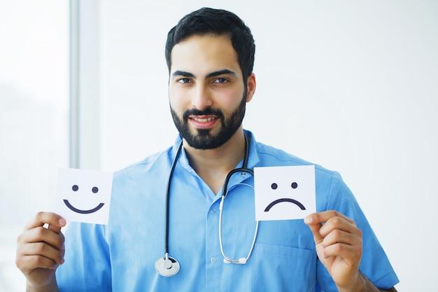 Gezondheidszorg. arts holding kaarten met symboolpret en droevige glimlach, medisch concept