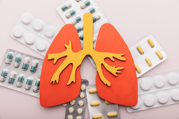 Gezondheidszorg concept long en pillen op roze achtergrond bovenaanzicht