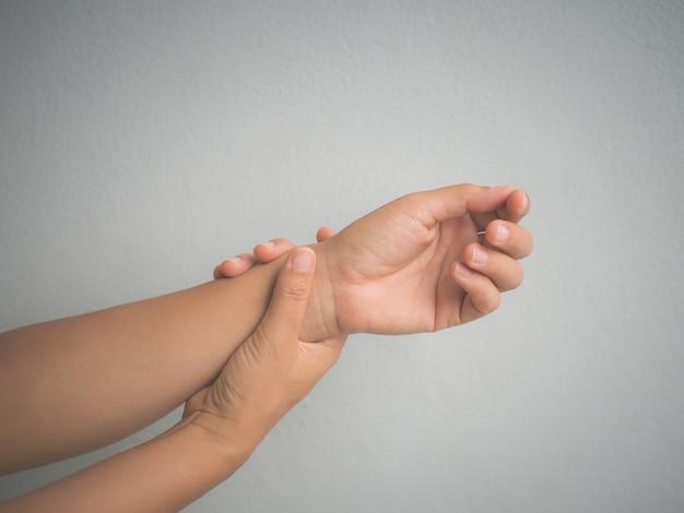 Gezondheidszorg concept. sluit vrouw omhoog haar symptomatisch het bureausyndroom van de pols houden.