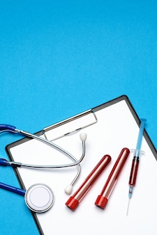 Gezondheidszorg concept - stethoscoop, bloed reageerbuis, spuit en klembord met blanco vel.