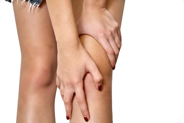 Gezondheidszorg concept. vrouw die aan pijn in knie lijdt. hand in hand op de knie. geïsoleerd