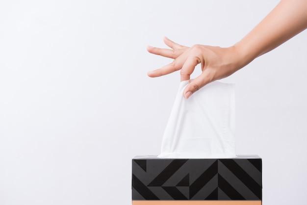 Gezondheidszorg concept. vrouw die wit papieren zakdoekje van doos met de hand plukken.