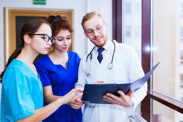Gezondheidszorg. een groep studenten geneeskunde communiceert voor een laptop. bespreking van de diagnose.