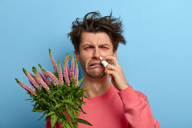 Gezondheidszorg en allergiesymptomen concept. ontevreden man geneest allergische rhinitis met neusdruppels, heeft een zieke uitdrukking veroorzaakt door trigger, geïrriteerde rode ogen, poseert binnenshuis, is overgevoelig