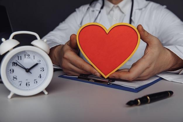 Gezondheidszorg en behandelingsconcept arts die een houten model van hart in zijn kantoor toont
