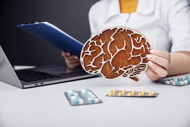 Gezondheidszorg en behandelingsconcept arts die houten model van de hersenen houdt