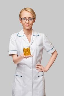 Gezondheidszorg en dieet concept - arts-voedingsdeskundige of cardioloog die visolie in capsules voor vitamine d en omega-3-vetzuren houdt