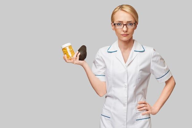 Gezondheidszorg en dieetconcept - arts-voedingsdeskundige of cardioloog die visolie in capsules voor vitamine d en omega-3-vetzuren en avocado houdt
