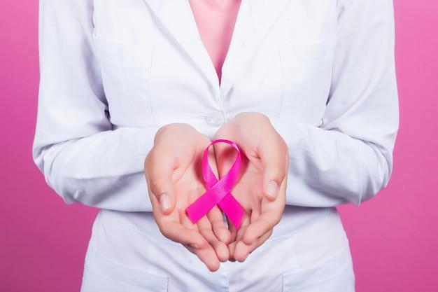 Gezondheidszorg en geneeskundeconcept - dameshanden die roze het voorlichtingslint van borstkanker houden.