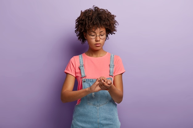 Gezondheidszorg en geneeskundeconcept. ernstige jonge vrouw met afro-kapsel houdt vingers op de pols
