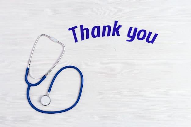 Gezondheidszorg en medisch concept, gekleurde stethoscoop blauw en tekst dank u