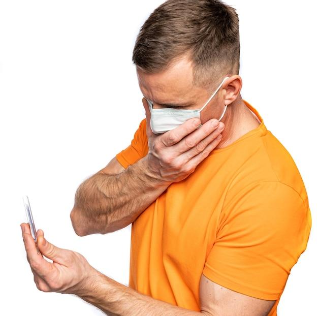 Gezondheidszorg en medisch concept. man in masker met thermometer in handen, lichaamstemperatuur meten terwijl hij aan griep lijdt. gefrustreerde man met thermometer die zich ziek voelt