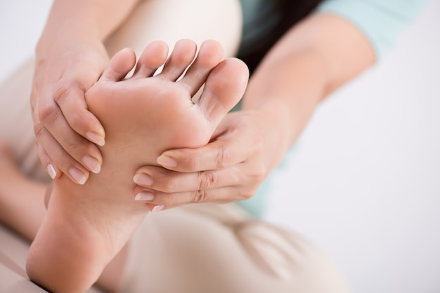 Gezondheidszorg en medisch concept. vrouw die haar pijnlijke voet masseert