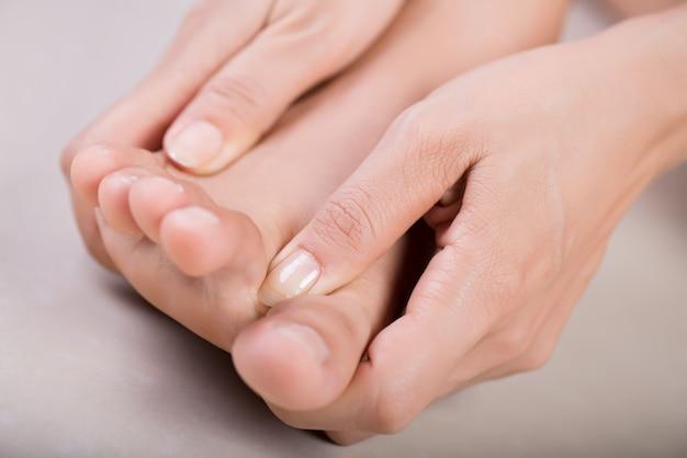 Gezondheidszorg en medisch concept. vrouw masseert haar pijnlijke voet