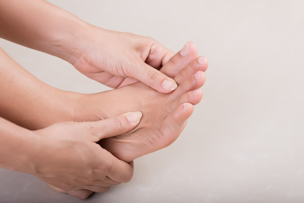 Gezondheidszorg en medisch. vrouw masseert haar pijnlijke voet.