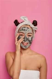 Gezondheidszorg en schoonheidsprocedures thuis. tevreden natuurlijke vrouw raakt gezicht aan, staat met aangebracht schoonheidsmasker, draagt hoofdband, heeft twee haarknopen, verfrist de huid graag, geïsoleerd op roze muur