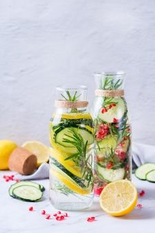 Gezondheidszorg, fitness, gezonde voeding dieet concept. verse koele citroen komkommer rozemarijn granaatappel doordrenkt water, detox drankje, limonade in een glazen pot voor lente zomerdagen.