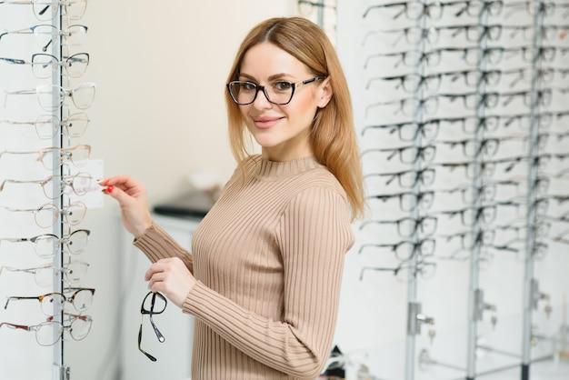 Gezondheidszorg, gezichtsvermogen en visie concept - gelukkige vrouw bril kiezen bij optica winkel. portret van mooie jonge vrouw die nieuwe glazen in opticienopslag probeert