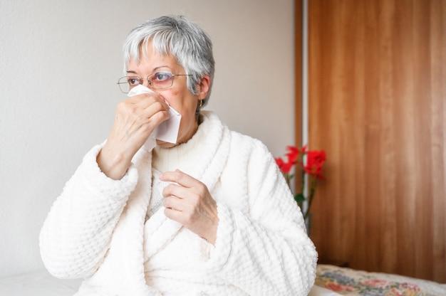 Gezondheidszorg, griep, hygiëne en mensenconcept. de zieke hogere vrouw met document veegt thuis blazend zijn neus af.