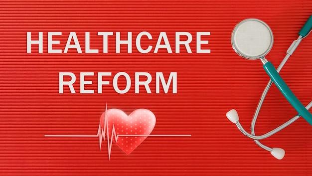 Gezondheidszorg hervormingsconcept met stethoscoop en hartvorm op een rode achtergrond