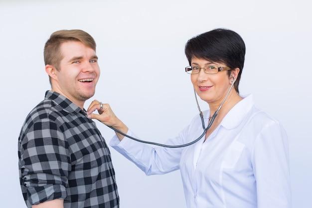 Gezondheidszorg, medisch examen, mensen en geneeskundeconcept - jonge man en arts met een stethoscoop