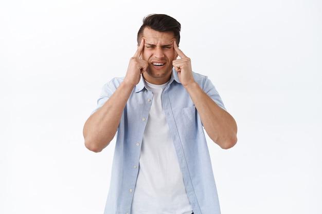 Gezondheidszorg mensen en emoties concept. portret van een knappe volwassen man die loenst en grimassen trekt omdat hij geen bord kan lezen zonder bril, slecht zicht heeft, opticien bezoekt om ogen te controleren, witte muur