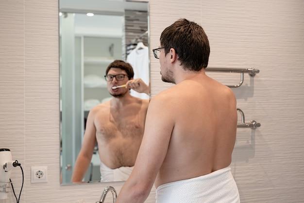 Gezondheidszorg, mondhygiëne. jonge volwassen man tandenpoetsen in de badkamer, kijkend naar de spiegel