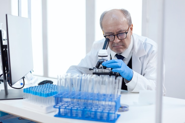 Gezondheidszorg senior wetenschapper man in de medische industrie die genetische analyse uitvoert met behulp van een microscoop. chemicus-onderzoeker in steriel laboratorium die experimenten doet voor de medische industrie met behulp van moderne technologie.