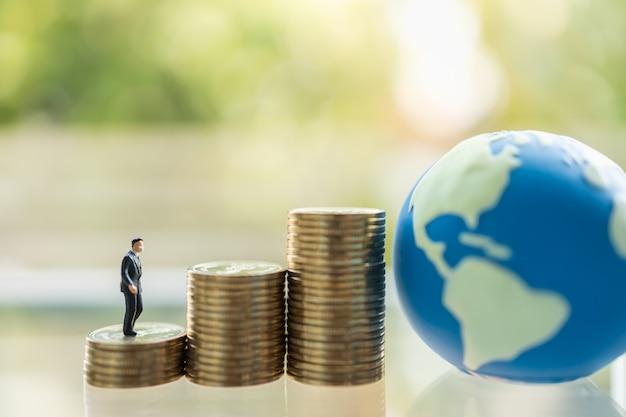 Gezondheidszorg, situatie bedrijfs- en economieconcept. mensen van het zakenman de miniatuurcijfer met gezichtsmasker die en zich op stapel gouden muntstukken met miniwereldbal bevinden lopen.