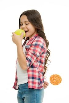 Gezondheidszorg trucs. kid meisje sluw eet appel terwijl lolly achter de rug houdt. wie ze probeert te misleiden. meisje doet alsof ze gezond voedsel eet als appel terwijl ze lolly verbergt als geheime traktatie.