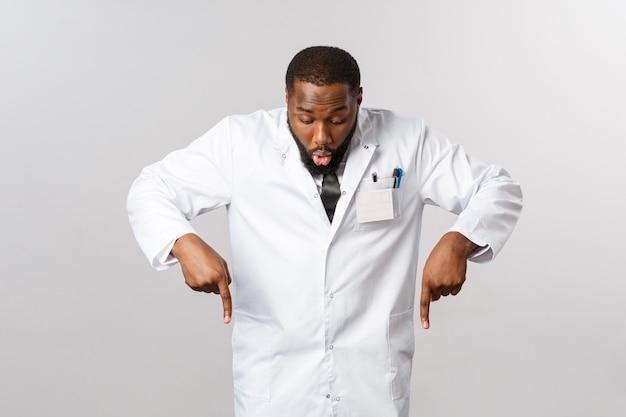 Gezondheidszorg, verzekeringen en kliniek concept. verbaasde en opgewonden afro-amerikaanse dokter in witte jas, hijgend geamuseerd, kijkend en wijzend met zijn vingers naar een geweldig product, geweldige kwaliteit, aan te bevelen