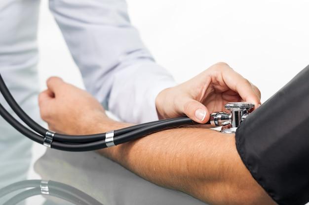 Gezondheidszorg, ziekenhuis en geneeskunde concept - arts en patiënt bloeddruk meten.