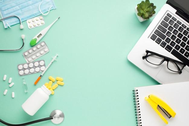 Gezondheidszorgapparatuur en kantoorbenodigdheden met vetplant op groene achtergrond