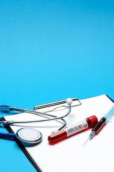 Gezondheidszorgconcept - covid-19 negatieve bloed reageerbuis, stethoscoop, spuit en klembord met