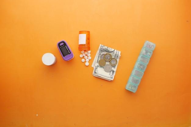 Gezondheidszorgkostenconcept met amerikaanse dollarcontainer en pillen op tafel