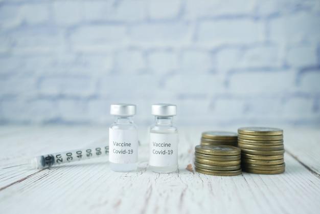 Gezondheidszorgkostenconcept met stapel munten en coronavaccin op tafel