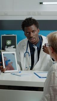 Gezondheidszorgspecialist die cardiogram op tabletdisplay uitlegt