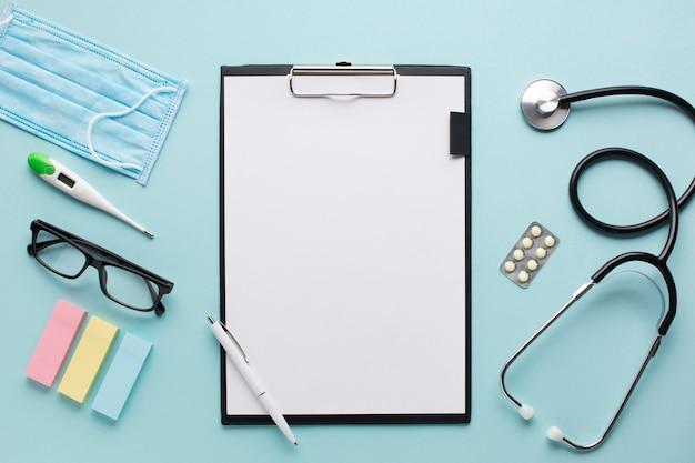 Gezondheidszorgtoebehoren bovenaanzicht dichtbij klembord met plankdocument en bril op achtergrond